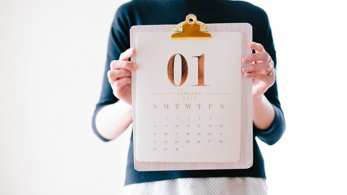 Woman holding up a clipboard with a January calendar on it