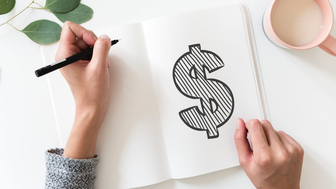 Dollar sign drawn into a journal with a person holding a pencil in their laft hand with coffee on the table