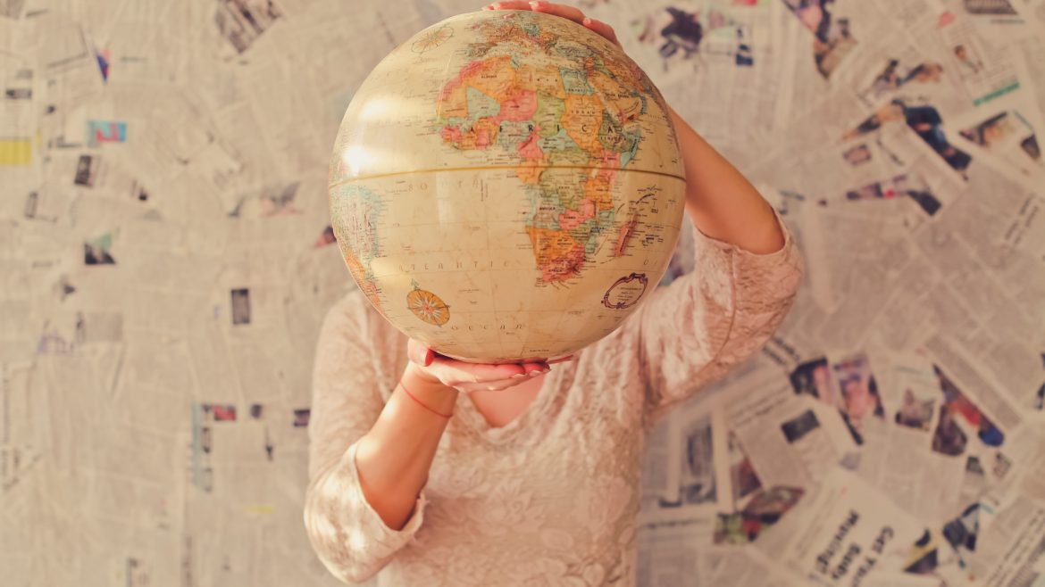 Person standing behind a globe covering face