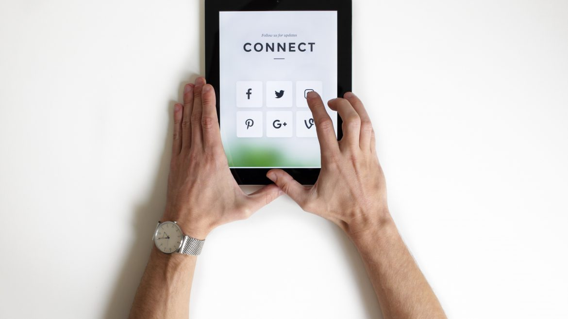 Man holding tablet with Connect and social media icons on it