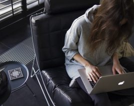 Woman sitting in a black chair with a laptop on her lap
