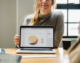 Woman behind a laptop that is facing the camera with a graph on it
