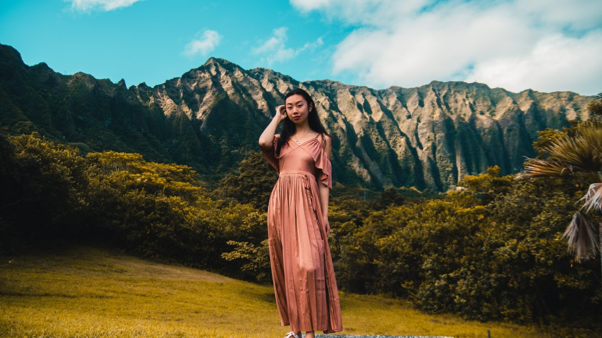 Woman standing on a hillside in a pink ankle length dress