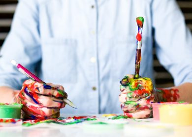 Person at a table with paint on hands and paintbrushes in hands