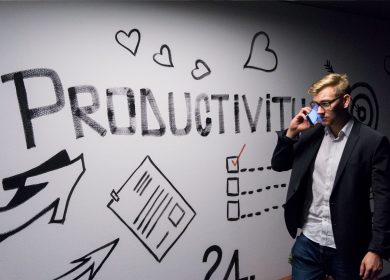 Wall with various images drawn on it including hearts and arrows with the word Productivity in the middle and a man on his phone walking next to it