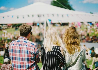 Three people faced away from camera looking off into a crowd with a tent