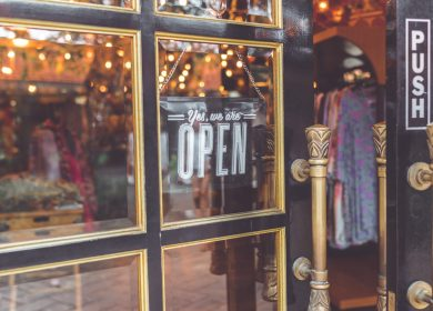 Shop window with the Open sign and door ajar with apparel in the background