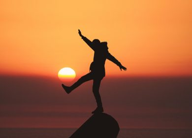Person standing on the top of a hillpoint with arms and leg out with the sunset in the background