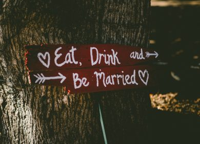 "Sign with the words ""Eat, Drink and Be Married"" on it against a tree"