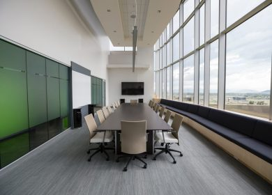 View from head of a conference table with green wall on the left and large windows to the right