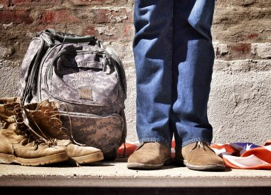 Legs of a person standing next to camoflauged backpack and combat boots