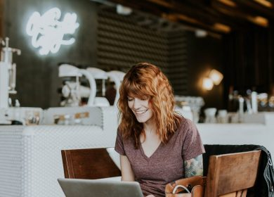 Red headed lady sitting in front of a laptop smiling facing the camera