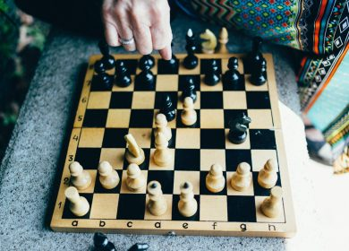 Chessboard with pieces on it and hand over it