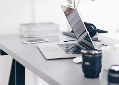 Desk with laptop and camera lenses on it