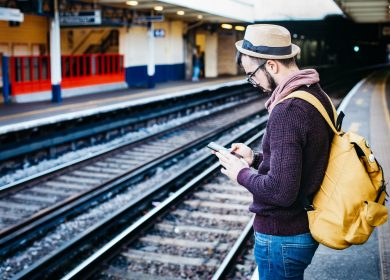 Man with hat and glasses wearing backpack standing near train tracks looking at phone