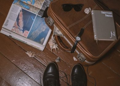 Travel book, suitecase, sunglasses, watch, pad and mens shoes