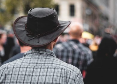 Back of man wearing a leather cowboy hat with plaid shirt with a crowd in the background