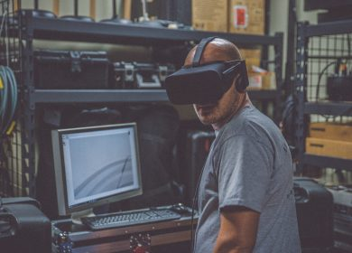 Man standing in front of compute with VR goggles on