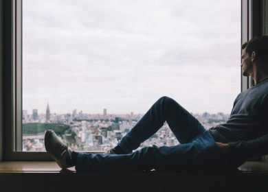Man sitting on window bench with legs up looking out at city view
