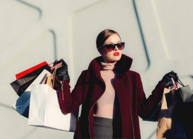 Woman wearing coat and sunglasses carrying bags