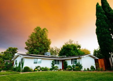 House with a yard against an orange sky background