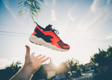 Red shoe floating in air with hand ready to catch it with the sun and sky in the background