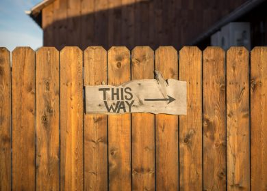 "Wood fence with Cardboard sign with words ""This Way"" and an arrow pointing to the right on it"