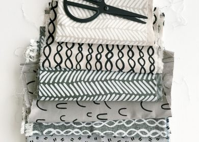 Neatly folded pile of different patterned fabric with scissors on top