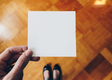 Person holding a blank square of paper