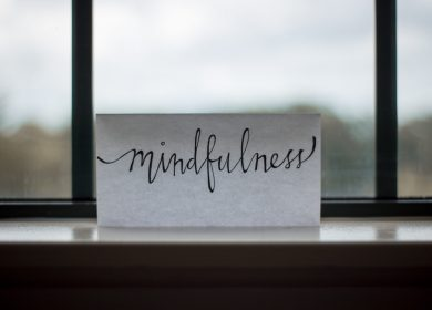 "Paper with the word ""mindfulness"" on it on a table in front of a window"