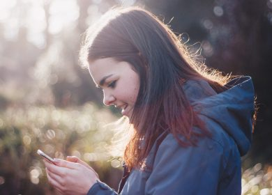 View of woman in blue hoodie from left side as she looks at a phone