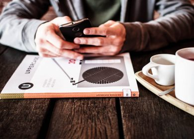 Hands holding a smartphone over booklet next to coffee