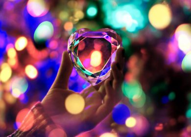 Hand holding up ornament with colorful lights in the background