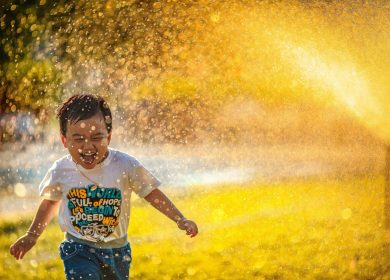 Boy running through water with white t-shirt and smile