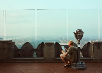 Man sitting on public viewing machine at the top of a building