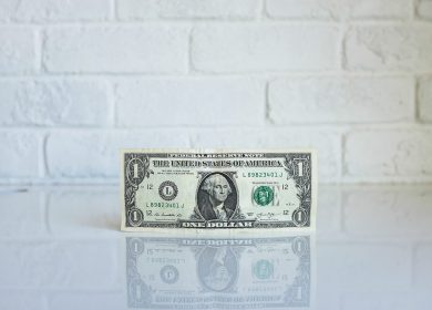 One Dollar Bill against a white brick background