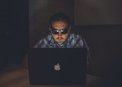 Man wearing dark glasses looking at laptop