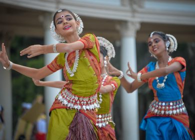 Three ladies in Indian dress dancing traditional dance