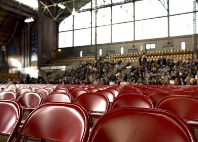 View of chairs set up with crowd in stands in the background