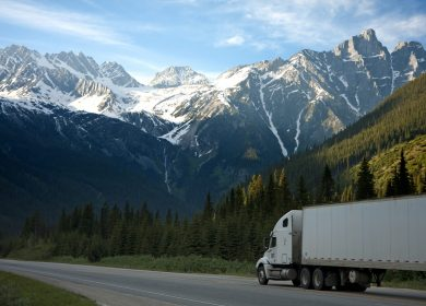 View of Semi-truck with trailer on a road with snow covered hills in the background