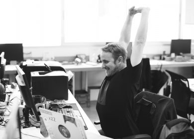 Man at desk with computer and printer stretching with arms in the air
