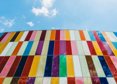 Wall with different colored panes with sky in the background