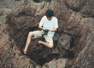 Man sitting on the side of a rock cllff looking at a camera