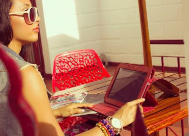 Woman sitting at table with tablet wearing glasses