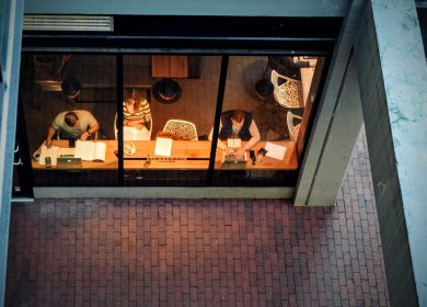 Top view of people inside a room with a long table set next to a large window
