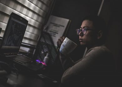 Man looking at laptop computer screen while holding a coffee cup close to his mouth