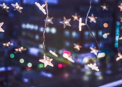 Star shaped stringed lights with building lights in the background